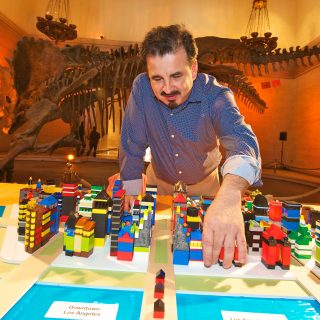 A man leans over a table with blocks depicting city streets and repositions a block.