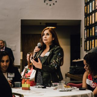 A woman stands at a table and asks a question using a microphone.