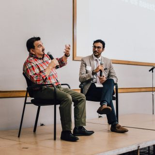 Two men sit on stage in chairs facing each other, and one answers a question.