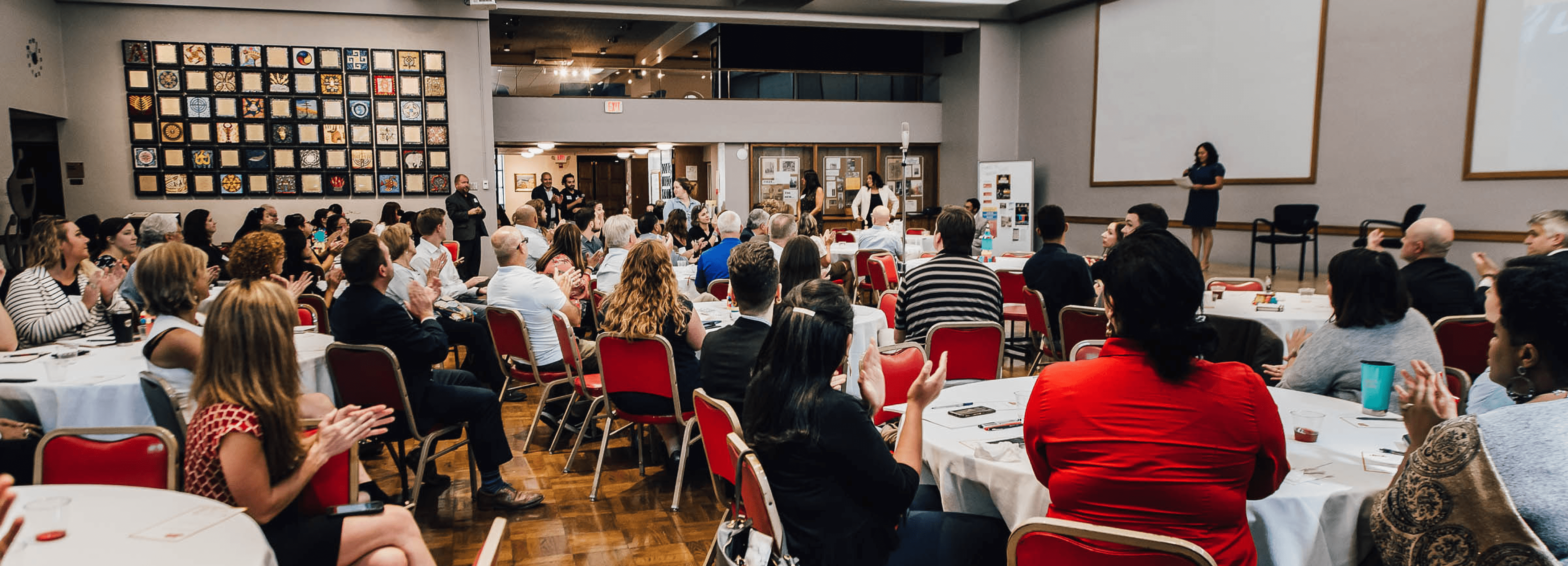 A group of people sit around tables at an event, applauding while a speaker reads on stage.