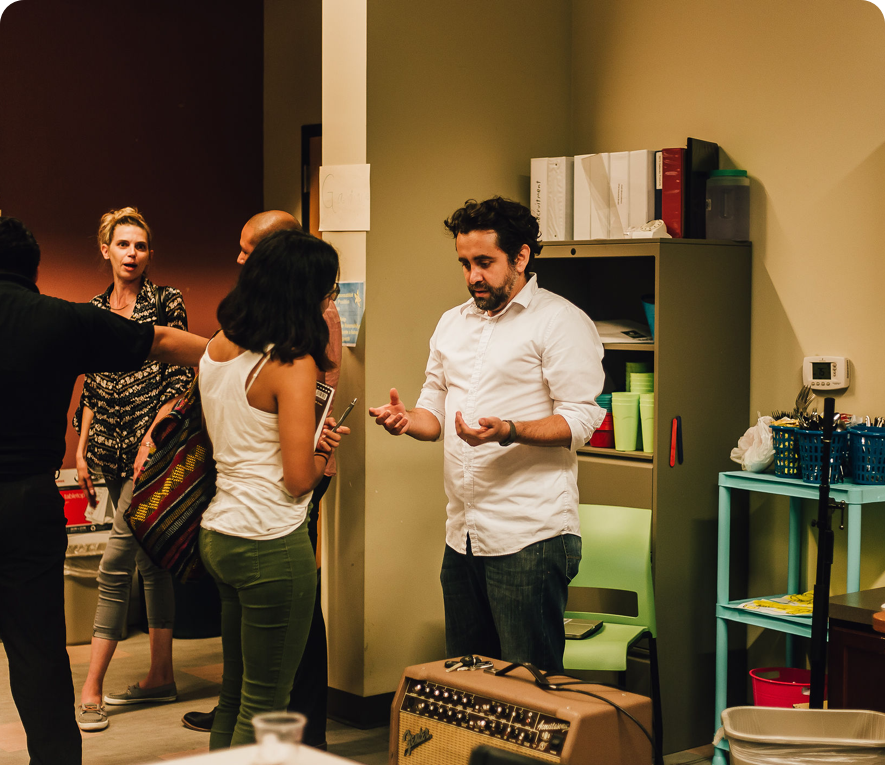 A man talks to a woman at an indoor event with other people socializing and milling around.