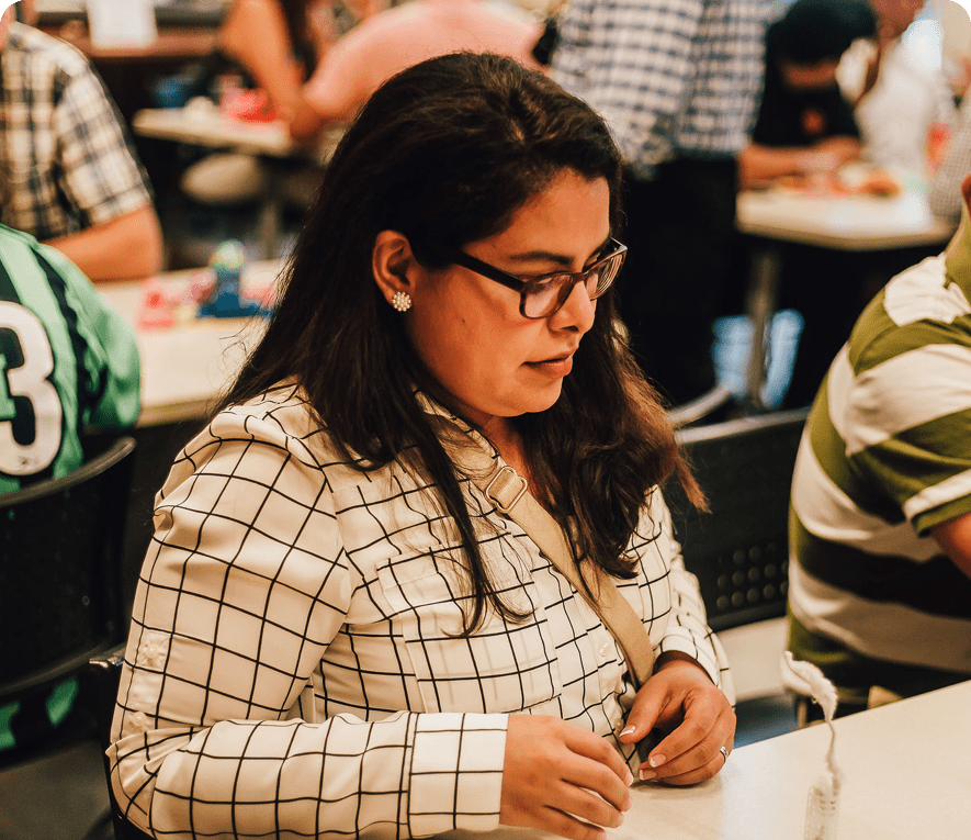 A professionally-dressed woman intently considers objects on a table during a workshop with other people.